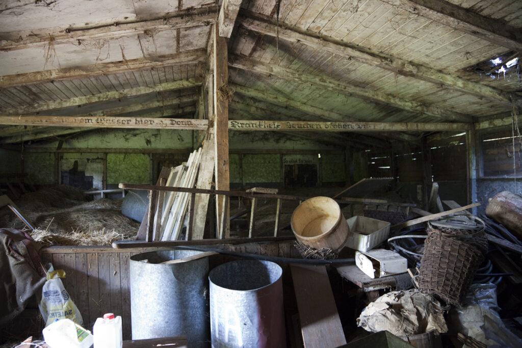 Interieur van een voormalige barak van het concentratiekamp Monowitz, nu een loods voor de rommel. Collectie Hans Citroen