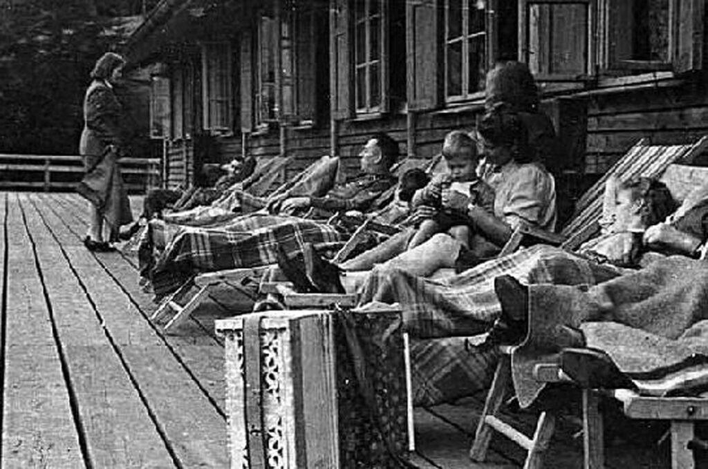 Des SS-Helferinnen – des auxiliaires féminines SS – se reposent lors d'une journée de détentee sur la terrasse de la Solahütte. Une des Helferinnen tient son fils de deux ans sur les genoux. 1944. Collection: United States Holocaust Memorial Museum
