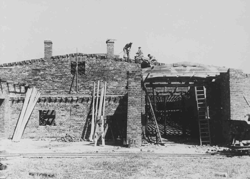 Construction des Kartoffelbarakken en été 1942. A l'horizon, la porte d'accès à Auschwitz-Birkenau. Collection : Panstwowe Muzeum Auschwitz-Birkenau